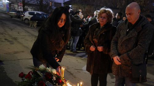 People light candles at the scene of Kosovo Serb politician Oliver Ivanovic's office. (AAP)