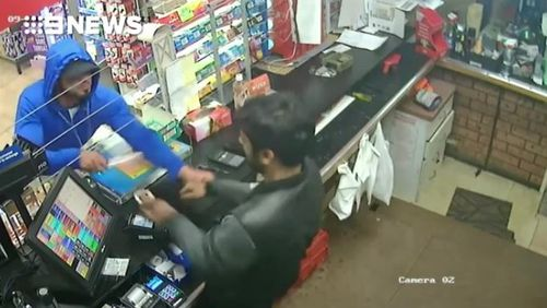 He grabs the cashier's hand while brandishing the knife.
